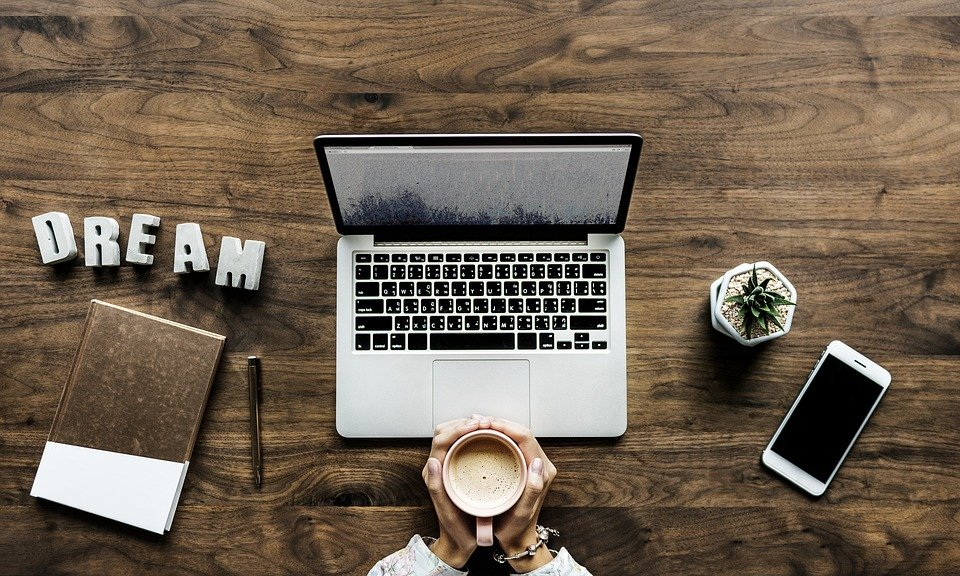 blogger sitting in front of a laptop with coffee